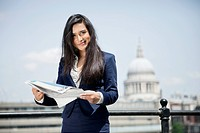 Portrait of Indian businesswoman holding newspaper with St. Paul´s Cathedral in background