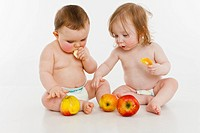 Two baby girls sitting together eating apples