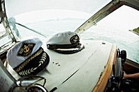 Two captain's hats resting on the dashboard of a motorboat, Avacha Bay, Russia