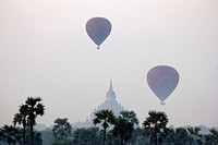 Hot air balloons in the sky of Bagan, temple in the background, Burma