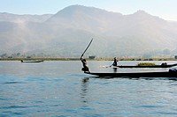 A Burmese fisherman swinging a stick on the end of a boat