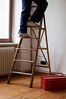 A man standing on a ladder, low section (thumbnail)