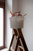 A bucket of painting equipment on a ladder