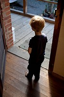 A young boy standing in an open doorway