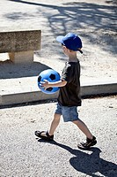 A young boy walking with a ball