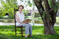 A senior woman reading next to a river