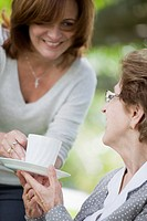 A woman handing a senior woman a cup of tea