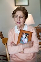 A senior woman holding a picture frame