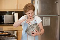 A senior woman mixing ingredients in a bowl