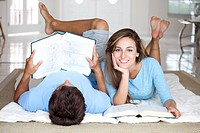 A young couple lying on the floor studying with textbooks (thumbnail)