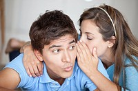 A man looking surprised at what his girlfriend is whispering in his ear