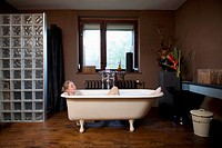 A woman taking a bubble bath in a claw foot tub