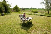 A woman with a laptop sitting at a table in her back yard, rural setting