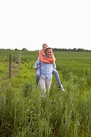 A man giving his girlfriend a piggy back ride through a field