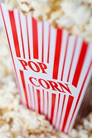 Detail of a red striped popcorn carton with Popcorn printed on it
