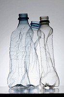 Three empty, partially crushed plastic water bottles