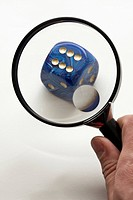 A hand holding a magnifying glass up to a dice