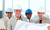 Smiling group of architect examining blueprints