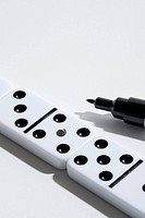 A domino with a fake dot on it, felt tip marker nearby