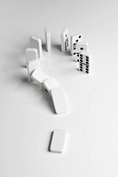 Dominoes arranged in a question mark falling over in a chain reaction