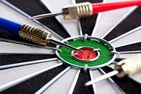 Extreme close up of three darts lying on their side around a bull's eye