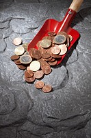 A red shovel with a heap of Euro coins