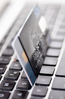Two credit cards balanced on a laptop keyboard, close_up