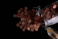 A glass jar spilling copper Euro coins (thumbnail)