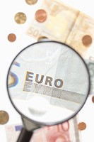 A magnifying glass magnifying a five Euro banknote