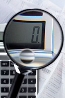 A magnifying glass magnifying a zero on a calculator on top of paperwork