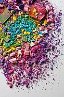 Various crushed up make_up powder products arranged in an abstract pattern