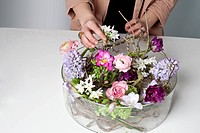 A florist arranging flowers in a glass bowel vase