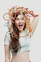 Portrait of shocked young woman's head tangled with colorful cables over gray background