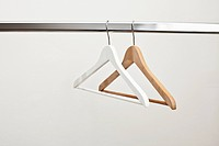 White and brown coat hanger on rail