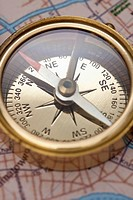 A compass on top of a road map, focus on compass