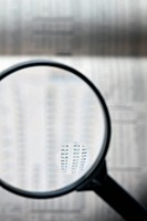 A magnifying glass magnifying stock market figure on a financial page