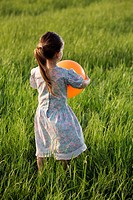 Rear view of a girl holding a balloon in a field