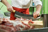 Detail of a man chopping meat with a large knife (thumbnail)