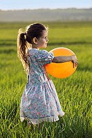Side view of a girl holding a balloon in a field