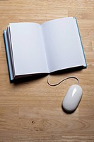 A hardcover book with a computer mouse attached to it (thumbnail)