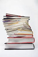 A variety of hardcover books arranged in a spiraling stack