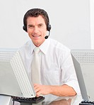 Smiling businessman with a headset on in a call center