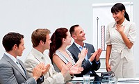 Business people applauding a colleague after giving a presentation