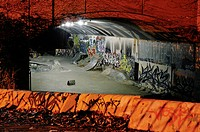 Skateboarding ramps and graffiti in a tunnel at night