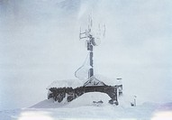 A building with a large antenna covered in snow