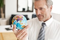 Businessman holding miniature globe