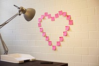Adhesive notes arranged into the shape of a heart on a wall next to a desk (thumbnail)