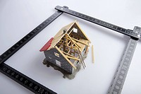 A partially constructed model of a house and a folding ruler