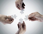 Four hands holding jigsaw puzzle pieces, directly above (thumbnail)