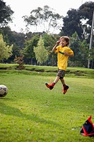 A young boy jumping in mid_air on a soccer field